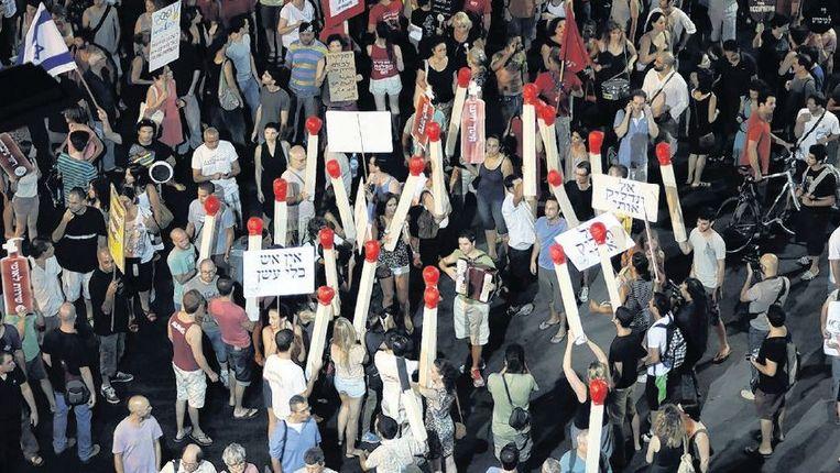 Protestmars in Tel Aviv, begin augustus. De lucifers verwijzen naar een eerdere zelfverbranding. Beeld afp