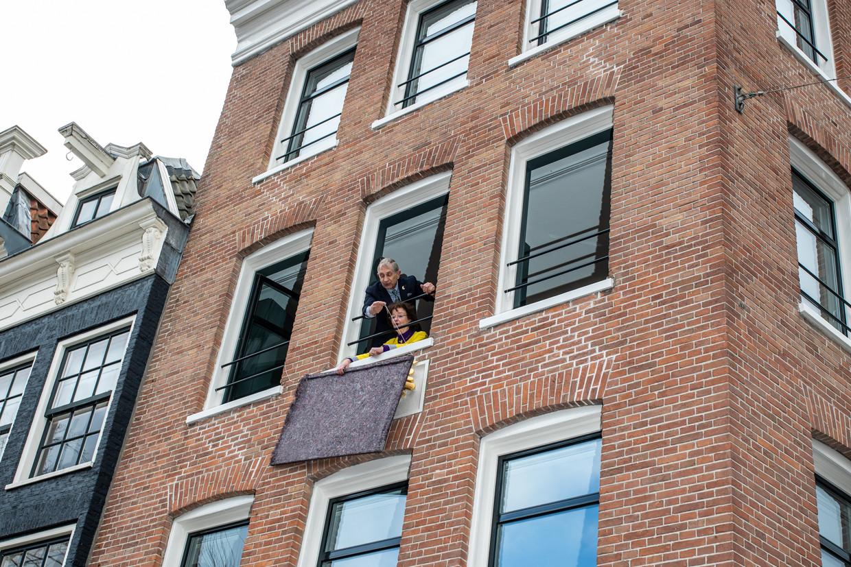 Anneke en Rudolph Schat, die zestig jaar op Spiegelgracht 20a woonden, onthullen de gevelsteen  – een eerbetoon aan hen. 'Krankzinnig leuk,' aldus Anneke. Beeld Nosh Neneh