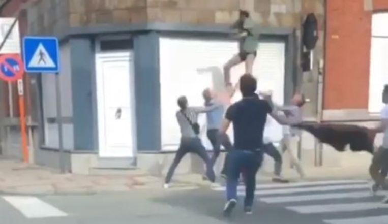 Mensen snellen toe om de vallende man op te vangen.