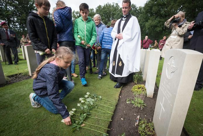 Leerlingen van 't Panorama leggen bloemen bij het graf van William Loney. Op de achtergrond predikant Brutus Green van het 2e Battalion The Parachute Regiment.