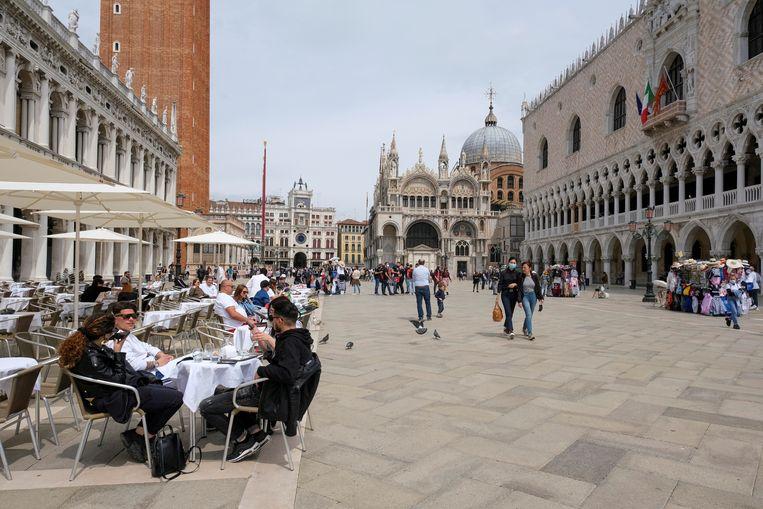 Mensen doen een terrasje op het San Marco-plein in Venetië. Italië blijft op dit moment dé trekpleister zonder rode zone. Beeld REUTERS