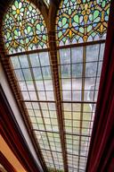 Hoge glas-in-loodramen in jugendstil geven de bibliotheek van Bovendonk glans.
