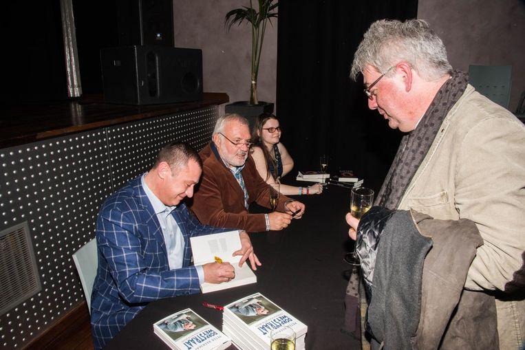Burgemeester Reekmans signeert een exemplaar.