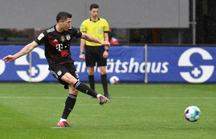 Robert Lewandowski schiet vanaf elf meter raak tegen SC Freiburg.