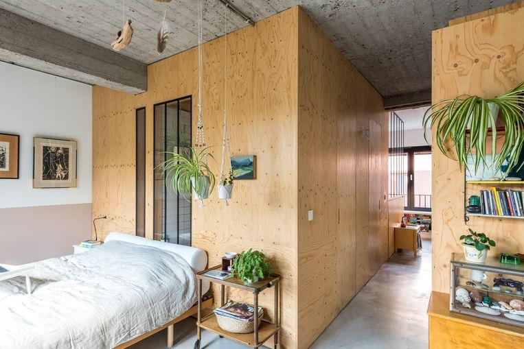 De woonruimte loopt over in Heidi's halfopen slaapkamer. In het achterste gedeelte van de loft bouwde ze drie houten volumes, met links en rechts de slaapkamers en in het midden een badkamer. In de badkamer van OSB voorzag Heidi vier lange, smalle ramen om het daglicht door te laten via de slaapkamer.  Beeld Luc Roymans
