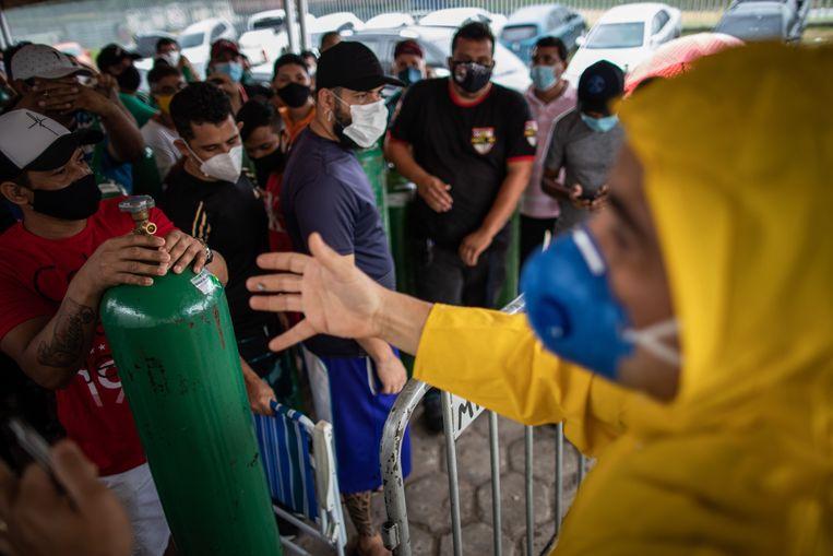 In de Braziliaanse stad Manaus staan familieleden van coronapatiënten in de rij om zuurstofflessen te vullen. Beeld EPA