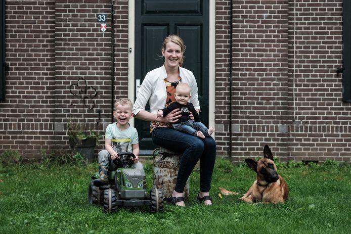 Boerin Nienke met zonen Tijmen (3) en Hidde (7 maanden) voor de boerderij.