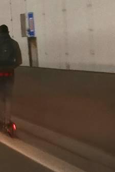 Un homme roule en trottinette électrique dans le tunnel Kennedy