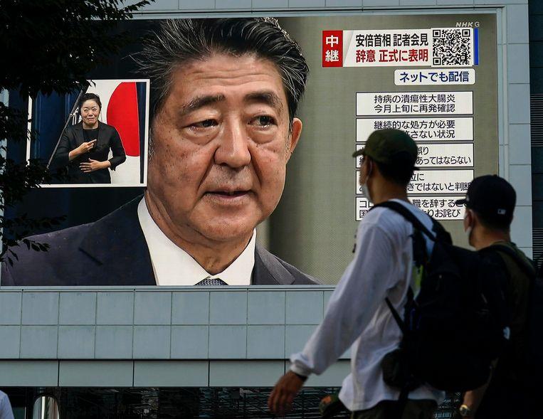Voorbijgangers in Tokio passeren een enorm tv-scherm waarop premier Abe zijn vertrek bekendmaakt.  Beeld EPA