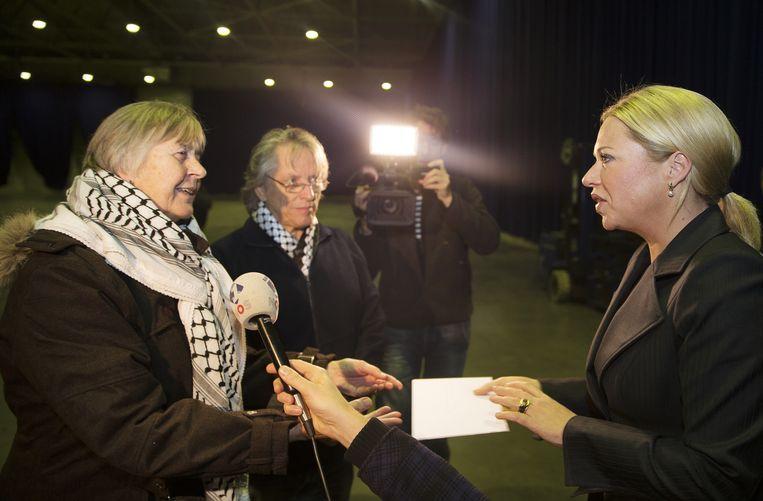 20 november 2014, Rotterdam: leden van het Samenwerkingsverband Stop Wapenbeurs overhandigen een petitie aan defensieminister Jeanine Hennis-Plasschaert (R). In Ahoy Rotterdam vond het jaarlijkse symposium van de Nederlandse Industrie voor Defensie en Veiligheid (NIDV) plaats. Beeld anp