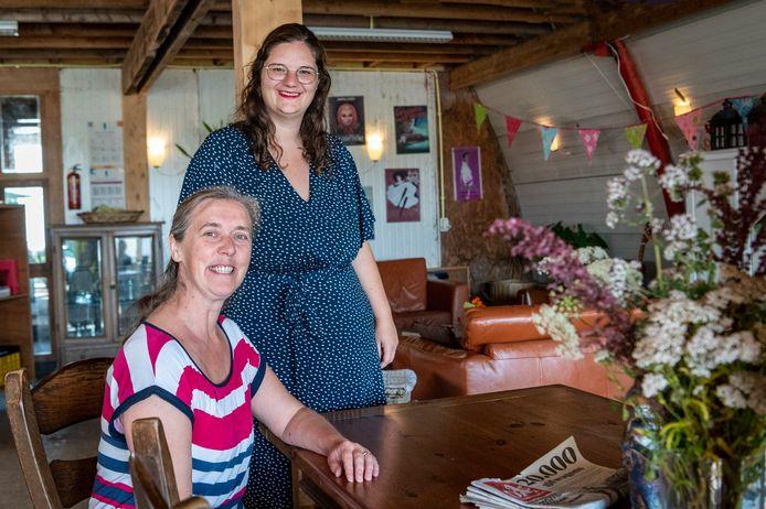Jolanda Vlieks en Mariska Harperink (blauwe jurk) in de oude loods die als buurthuis dient.