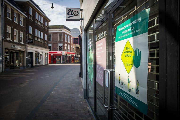 Een aanplakbiljet dat aangeeft dat klanten 1,5 meter afstand moeten bewaren in een winkelstraat in Haarlem.  Beeld ANP