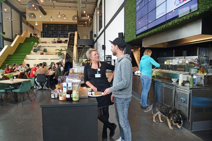 Zicht op de kantine van YourSurprise, waar gastvrouw Beatrijs Kreuzen dagelijks de maaltijden serveert. Naast haar staat Pieter van de Vate. Op de achtergrond is de zwarte glijbaan zichtbaar.