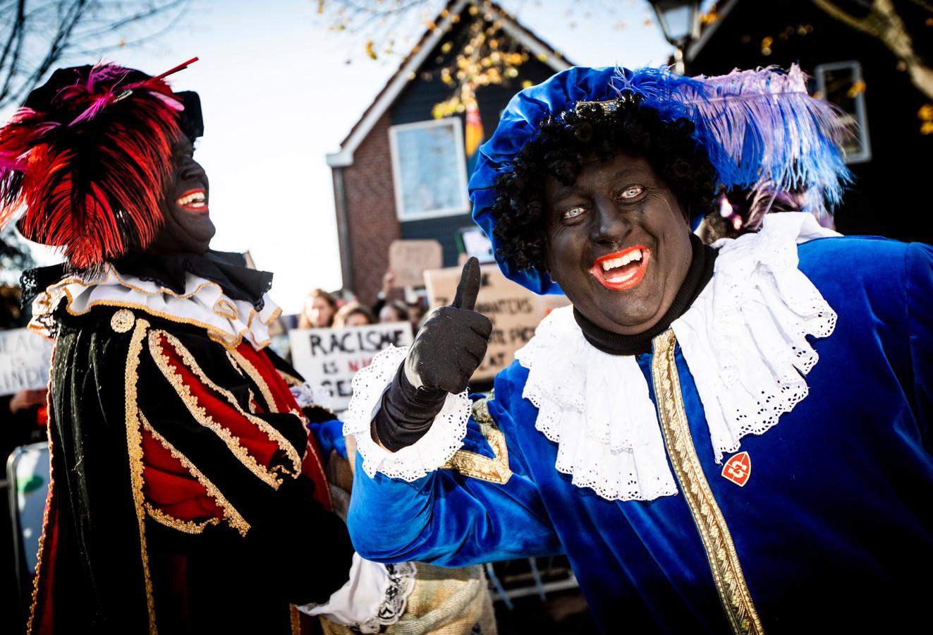 Demonstranten en zwarte pieten tijdens de landelijke intocht van Sinterklaas in de Zaanse Schans in 2018.