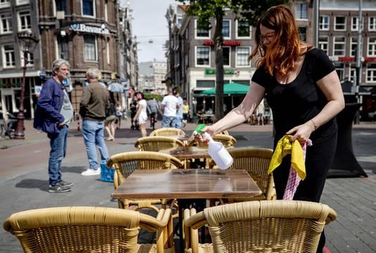 Een medewerkster desinfecteert een tafel op een terras aan het Amsterdamse Rembrandtplein.