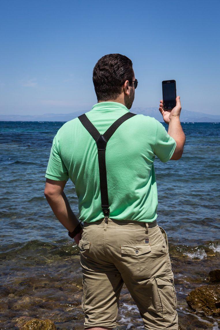 Abu Saif maakt een foto van de zee met aan de overkant Turkije. De plek waar hij de oversteek maakte op een bootje. Beeld Cigdem Yuksel