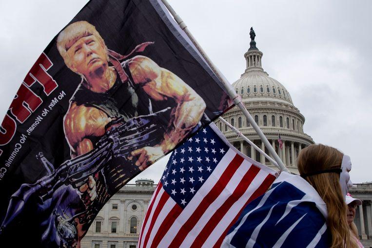 Een supporter van Trump draagt een vlag waarop hij is afgebeeld als Rambo. Beeld EPA