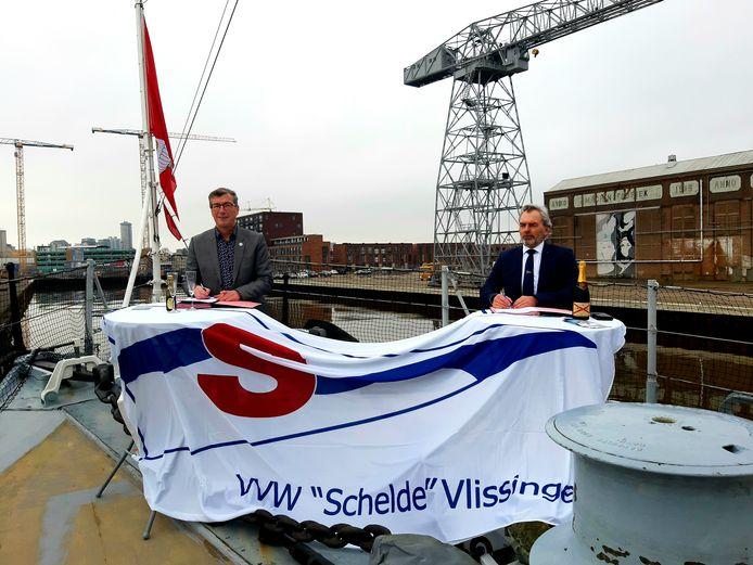 Wethouder John de Jonge (links) en voorzitter Sal Cracau van watersportvereniging Schelde tekenen de beheerovereenkomst voor de jachthaven Scheldekwartier op de voorplecht van museumschip De Mercuur in het Dok in Vlissingen.