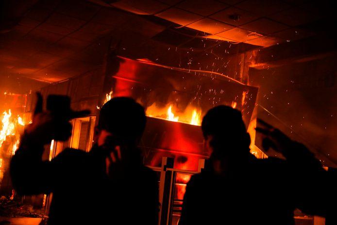 Demonstranten maken handgebaren voor het brandende Macul-metrostation.