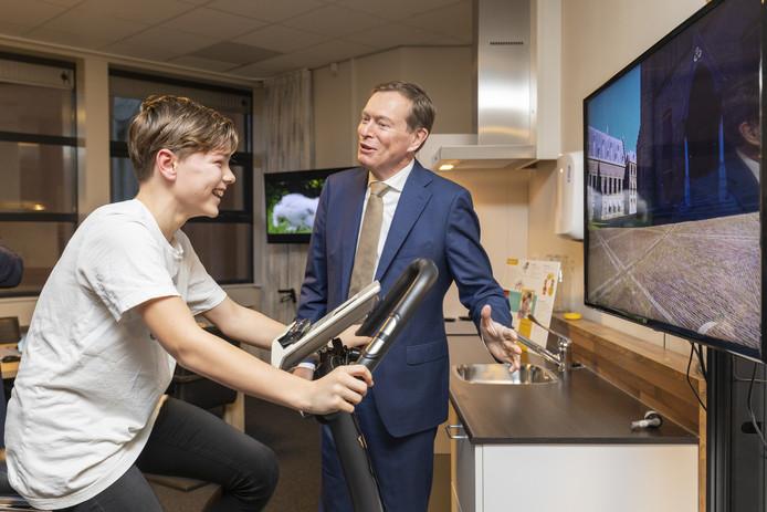 Minister Bruno Bruins ziet hoe astmapatiënt Sam de Vries virtueel door Den Haag fietst.