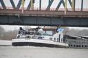 Een schipper heeft zijn stuurhut laten zakken en kan op deze manier toch onder het hefgedeelte doorvaren. De brug even aanraken is een uitdaging die schippers niet vaak kunnen weerstaan.
