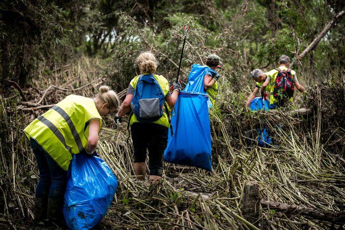 Een grote groep vrijwilligers zoekt onder begeleiding van boswachters van Natuurmonumenten naar troep tijdens een grote schoonmaakactie in de gebieden rondom de Maas.