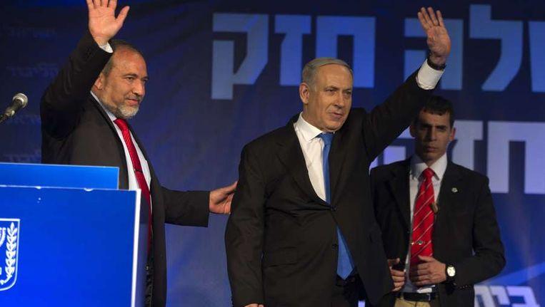 De Israelische premier Netanyahu (midden) zwaait naar zijn publiek tijdens de verkiezingsuitslag Beeld ANP