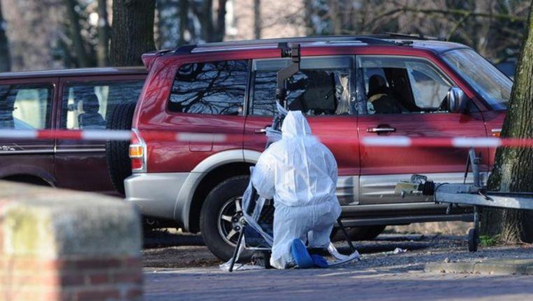 Een forensisch onderzoeker bekijkt maandag de plek in Amsterdam-Oost waar topcrimineel Stanley Hillis is neergeschoten. Beeld anp