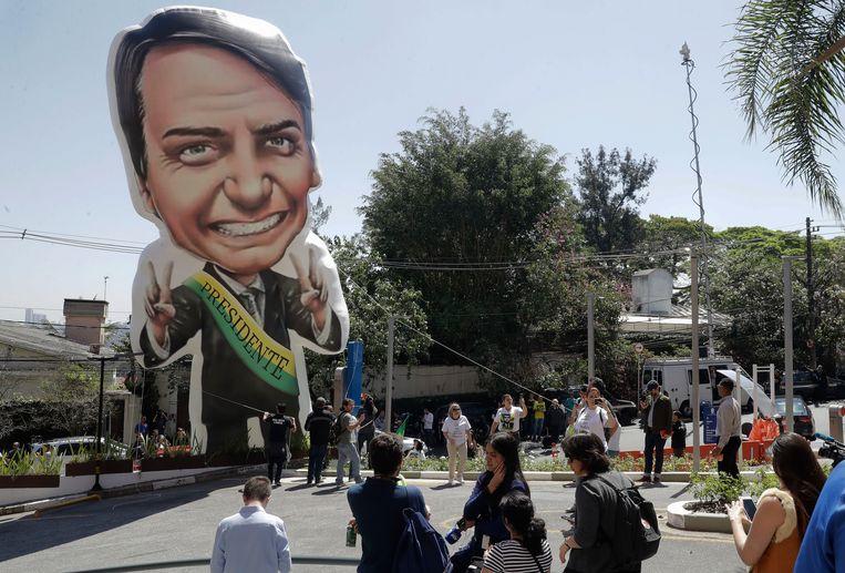 Aanhangers van de Jair Bolsonaro (l.) houden een wake voor het ziekenhuis in São Paulo waar hij is opgenomen. Beeld AP