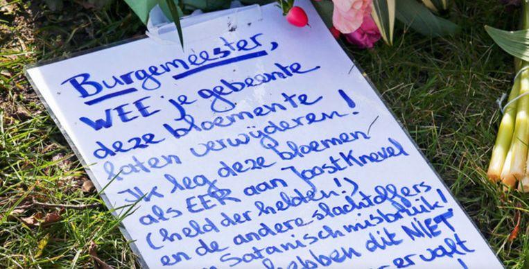 Een 'waarschuwingsbrief' van een van de bloemenleggers aan de gemeente zoals die te vinden was op het kerkhof in Bodegraven. Beeld AD