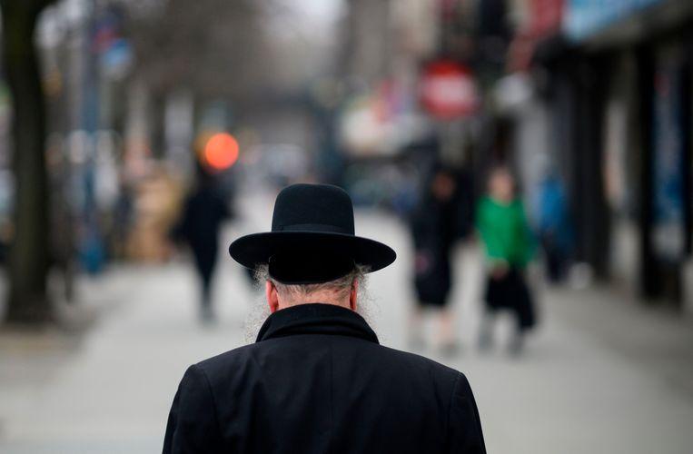 Een Joodse man steekt de straat over in Williamsburg, een wijk in Brooklyn waar de noodtoestand is uitgeroepen wegens een mazelenuitbraak. Beeld AFP
