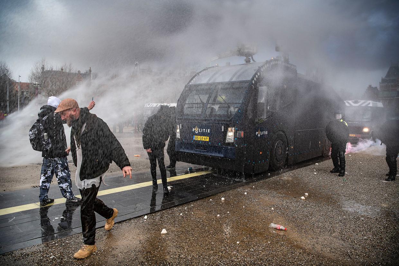 Enkele honderden demonstranten weigerden zondag te vertrekken van het Museumplein in Amsterdam, totdat de politie het waterkanon inzet en tientallen ME'ers de menigte terugduwen. Beeld Guus Dubbelman / de Volkskrant