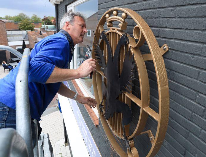 Peter van Vugt bevestigt de adelaar op het oude gemeentewapen.