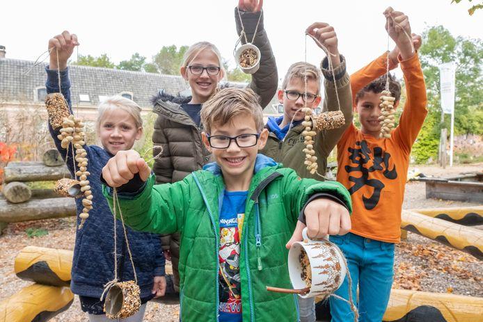Emy, Sanne, Mathijs, Kas en Joris (vlnr) laten de feestmaaltijden zien waar vogels in tuinen in Son en Breughel aan het eind van de herfstvakantie van kunnen genieten.
