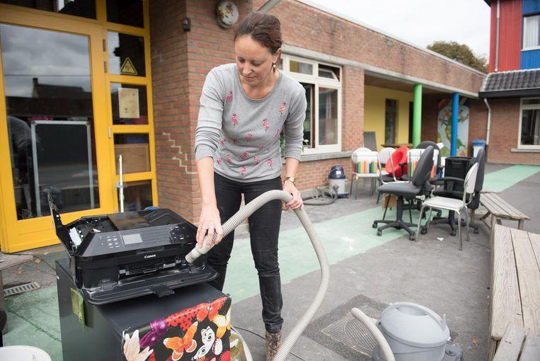 Directeur Freya Neyt probeert met een stofzuiger de printer weer proper te krijgen.