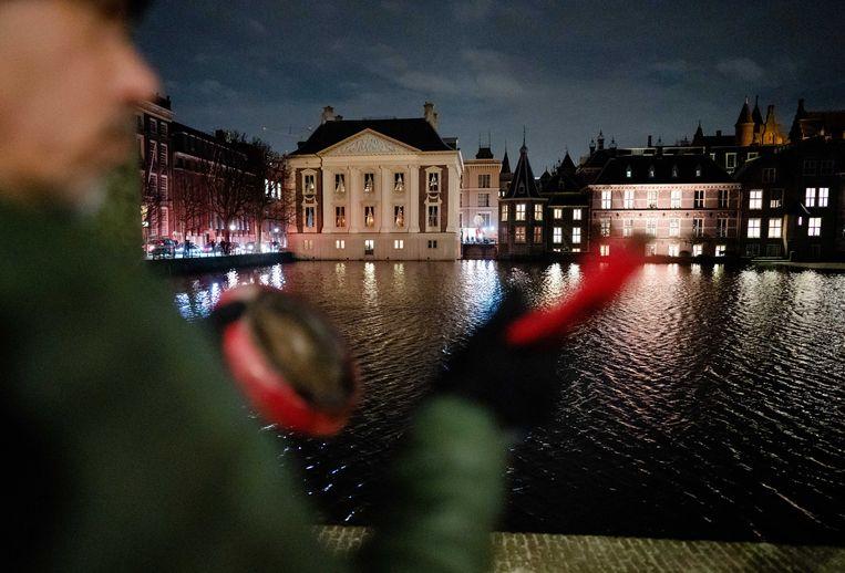Een groepje tegenstanders van de coronamaatregelen liet zich maandagavond bij de Hofvijver horen tijdens de toespraak van premier Mark Rutte. Beeld ANP