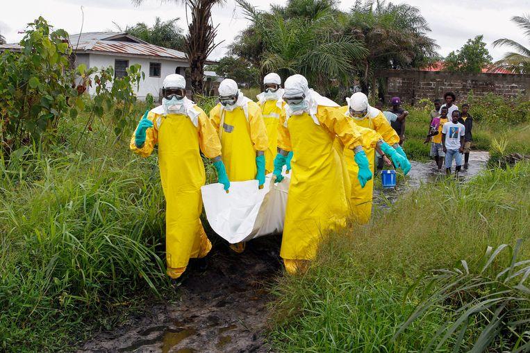 Verplegers in Libië dragen het lichaam van een ebola-slachtoffer. Beeld EPA