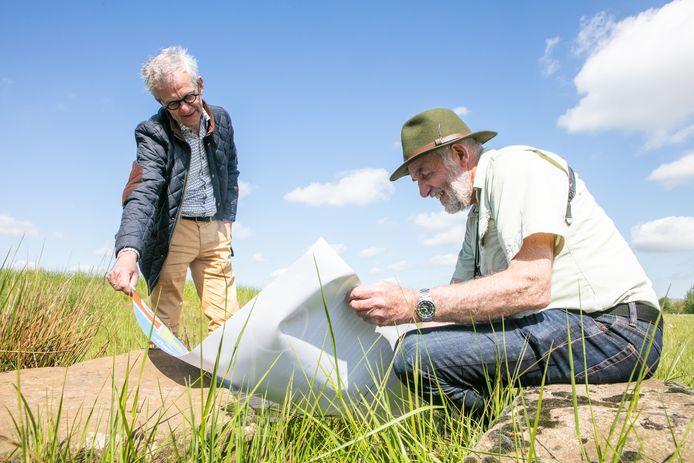 Arend Spijker (met hoed) en Gerrit Jan Bolks van Burgerinitiatief Ommen tonen het natuurontwikkelingsplan Ommermars. Na de bouwvak gaat de schop in de grond.