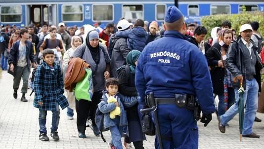 Vluchtelingen passeren een Hongaarse politieagent na hun aankomst op het station van Hegeyshalom.