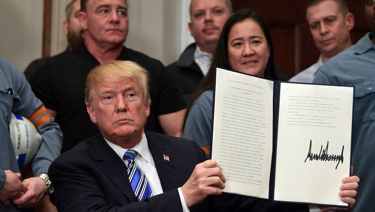 De Amerikaanse president Trump, omringd door staalarbeiders, heeft het decreet ondertekent voor de heffingen op geïmporteerd staal en aluminium. Beeld ap