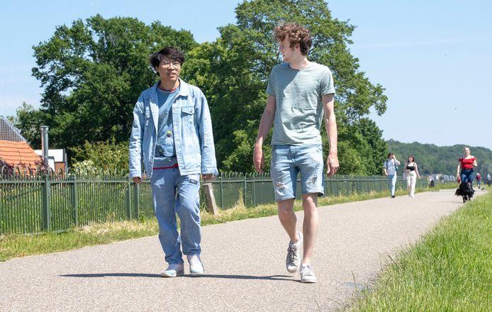 Zezhu Zeev (links) en Lennart Menssink (rechts) wandelen over de dijk in Wageningen