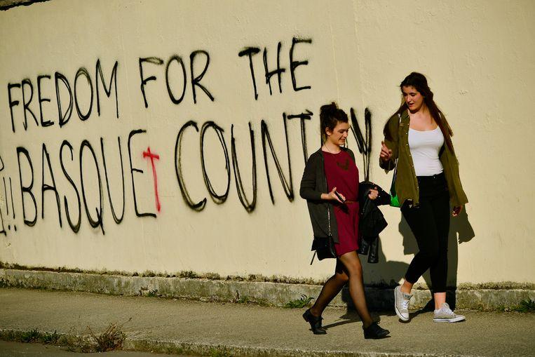 Twee vrouwen in de Spaanse stad Burlada lopen langs een muur waarop de steun uitgesproken wordt voor de afscheidingsbeweging Eta. Beeld AP