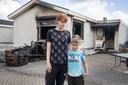 Priscillia Pril en haar zoonin bij de uitgebrande woonwagen. Die vloog vanmorgen in brand. Ze hebben bijna niets meer.