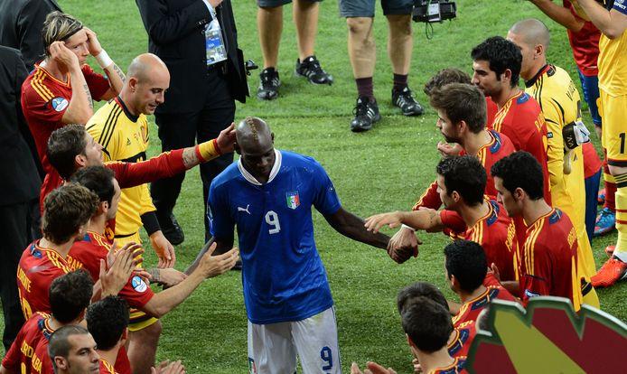 Mario Balotelli wordt getroost door de spelers van Spanje.