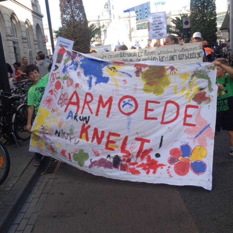 """Betogers dragen een spandoek met """"Armoede knelt""""."""
