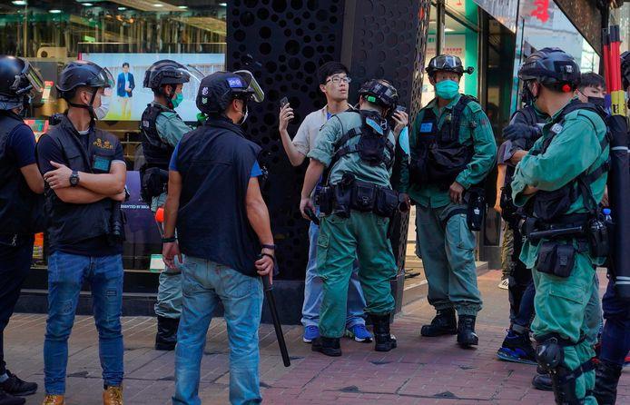 Een protestvoerder wordt aangehouden en gefouilleerd.