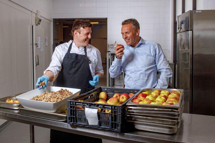 Jan Willem Poot (rechts) en chef-kok Bart Janssen die bij Yes We Can Clinics bezig zijn met 170 nagerechtjes voor fellows en personeel: appel met kwark en muesli, noten en zaden uit de oven.