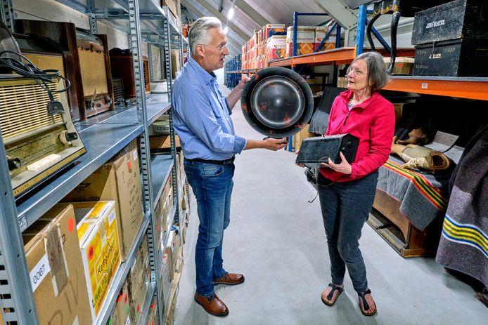 Museumdirecteur Dirk-Jan List en hoofd collectie Gerda Hitzert buigen zich in het nieuwe depot over een honderd jaar oude Philipsradio met een bijzondere ronde luidspreker.