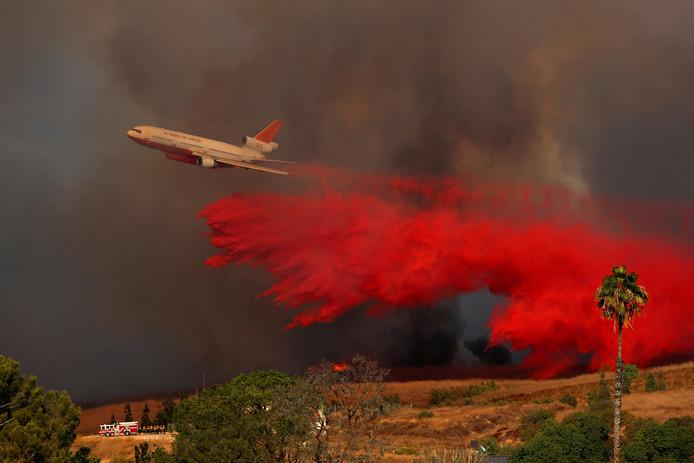 Een DC-10 lost bluswater bij een bosbrand in de Californische plaats Orange.  Foto Mike Blake