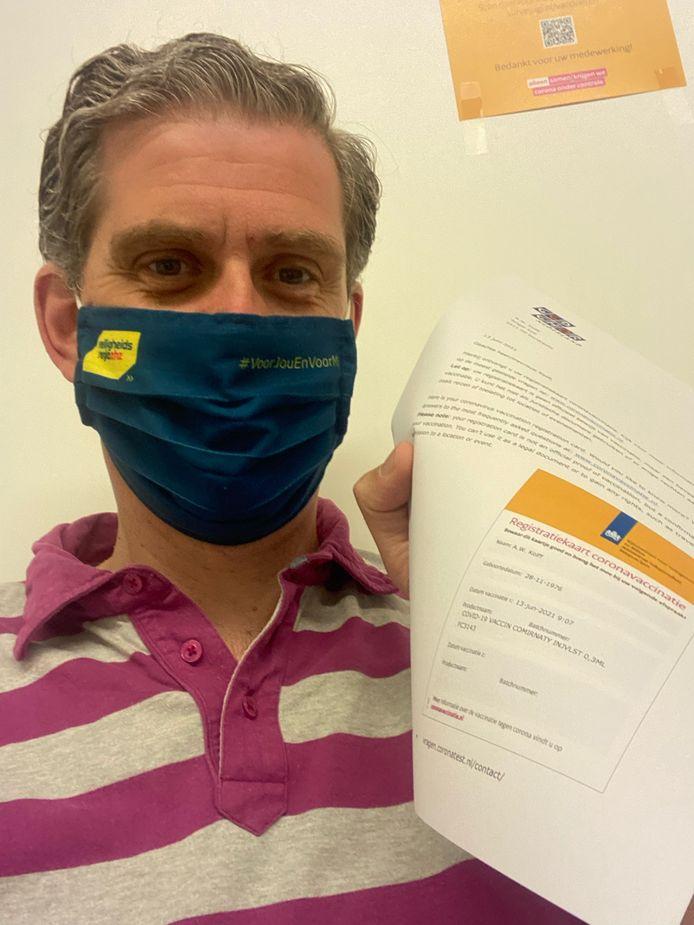 Burgemeester Wouter Kolff toont zijn registratiekaart voor het coronavaccin.